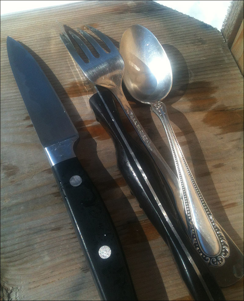 Clean utensils - two knives, a fork, a spoon, drying in the sun.