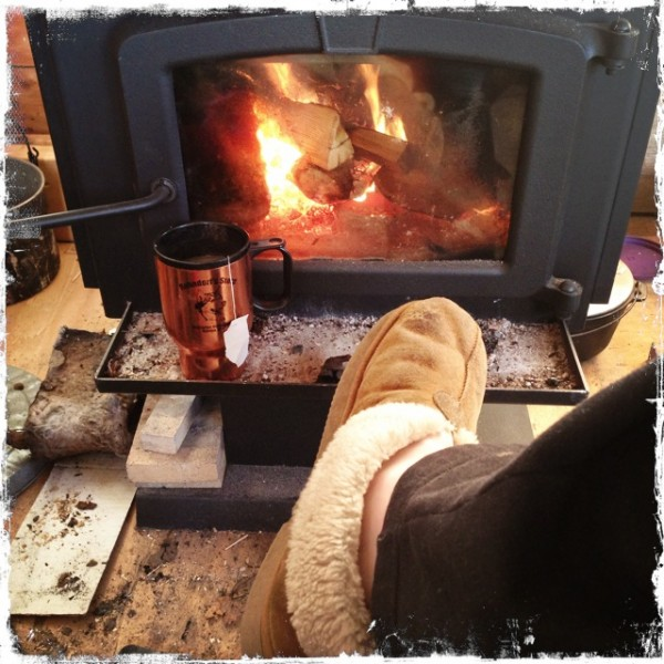 Cozy in front of a wood stove with a cup of tea.